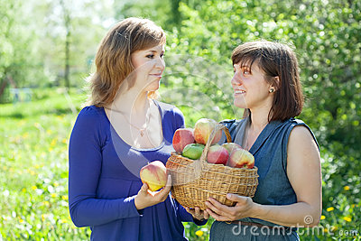 Girls with apples  in garden