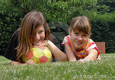 Girls with the ball lying on the grass