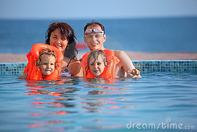 Girls bathing in lifejackets with parents in pool