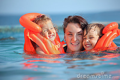 Girls bathing in lifejackets with woman in pool