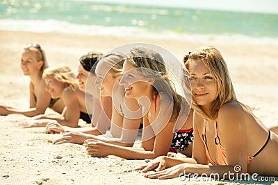 Girls in bikini lying on beach