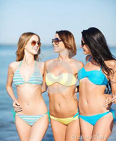 Girls in bikinis walking on the beach