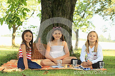 Girls on blanket having picnic