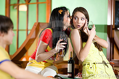 Girls with boy are drinking red wine