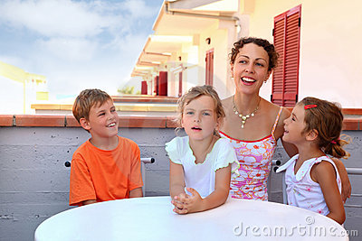 Girls with boy and mother sit on balcony