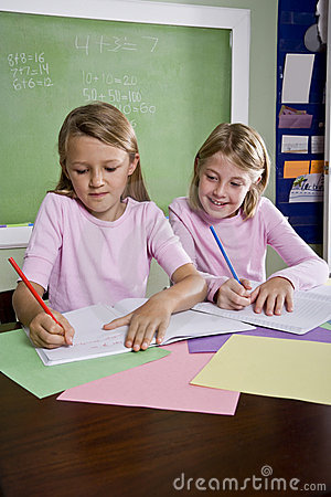 Girls in classroom doing schoolwork, writing