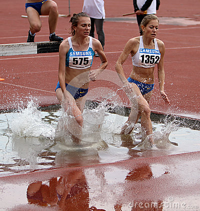 Girls compete in the 3.000 Meter Steeplechase Editorial Stock Photo
