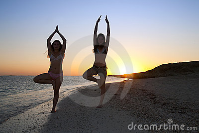 Girls doing yoga against sunset