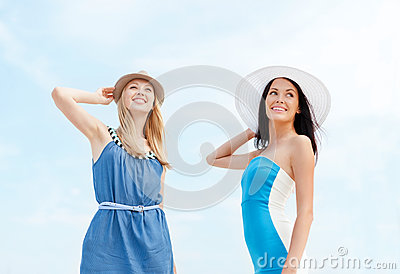 Girls in dresses with hats on the beach