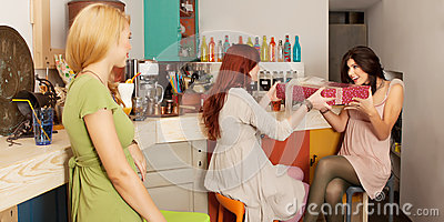 Girls exchanging gifts in colorful cafe