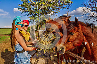 Girls feeding her horses