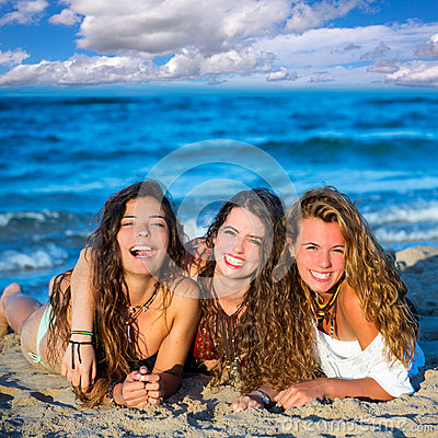 Girls friends having fun happy lying on the beach