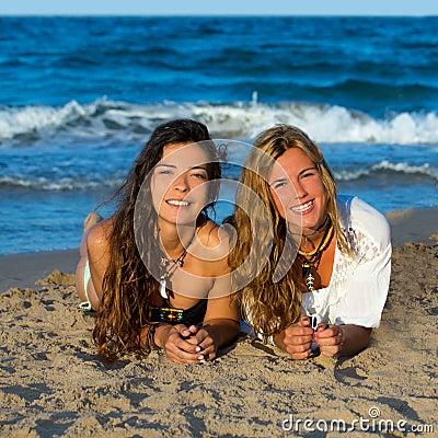 Girls friends having fun happy lying on the beach