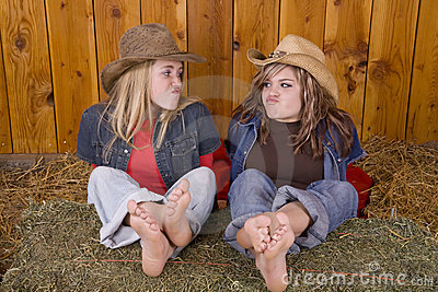 Girls funny face feet on hay