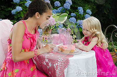 Girls in garden frosting cupcakes