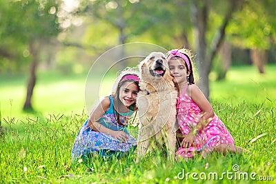 Girls hugging golden retriever in the park