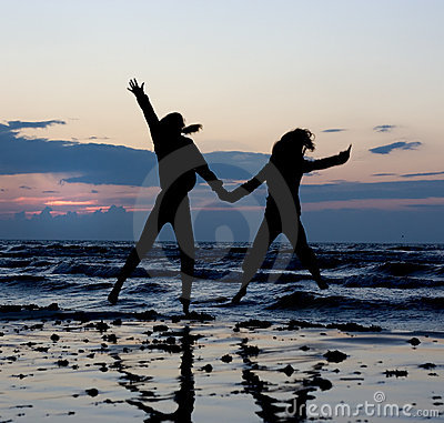Girls jumping near sea.