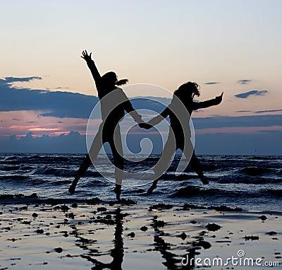 Girls jumping near sea.