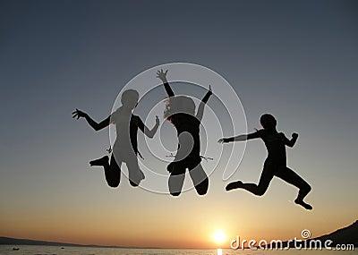 Girls jumping in sunset