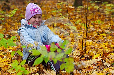 Girls kid smiling in autumn leaves background