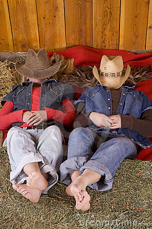 Girls laying with hats over heads feet on hay