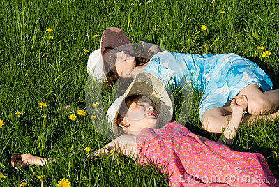 Girls lie on the grass, in nature