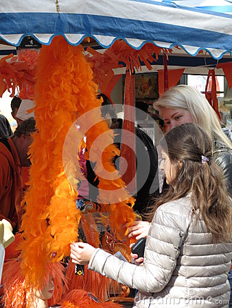 Amsterdam, Girls looking at an orange feather boa Editorial Stock Photo