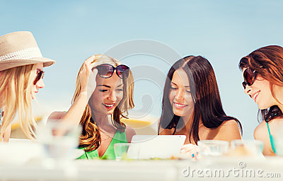 Girls looking at tablet pc in cafe