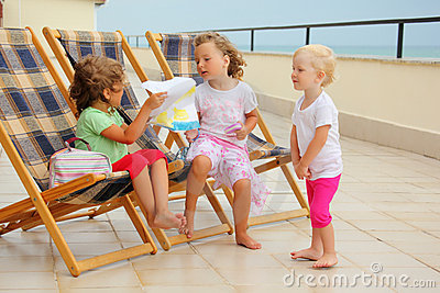 Girls in lounge on veranda, considering drawing