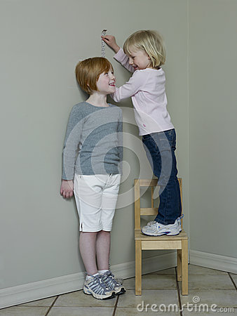 Girls Measuring Height Against Wall
