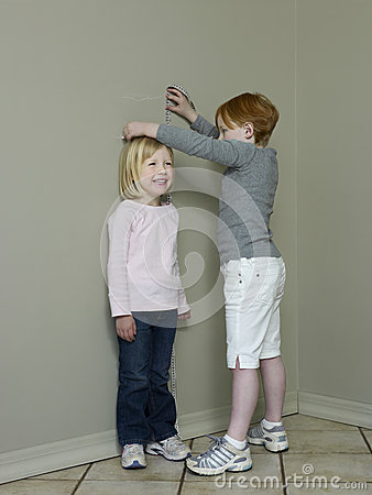 Girls Measuring Height Difference Against Wall