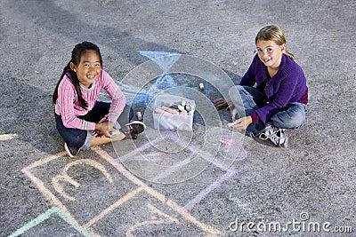 Girls playing with sidewalk chalk