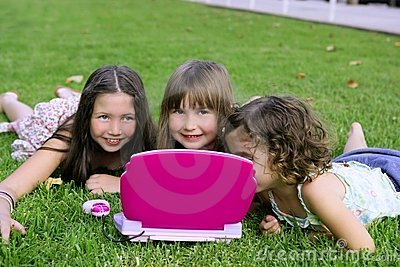 Girls playing with toy computer in grass