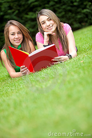 Girls reading a book outdoors