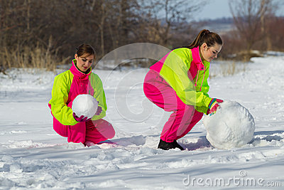 Girls rolling a huge snowbal