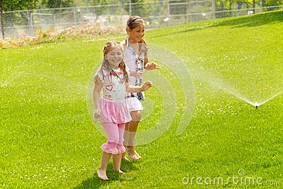 Girls run barefoot on a grass under splashes