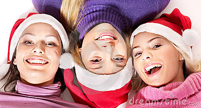 Girls in santa hat lying head next to head.