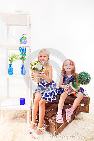 Girls sit on wooden boxes