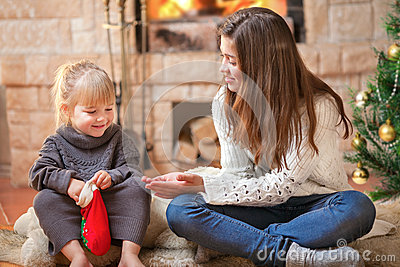 Girls sitting fireside opening Christmas presents