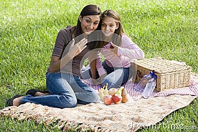 Girls sitting on picnic blanket on grass in park
