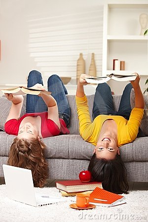 Girls smiling upside down on sofa