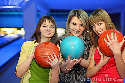 Girls stand alongside, hold balls for bowling