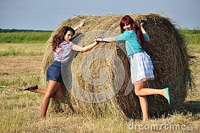 Girls standing by haystacks