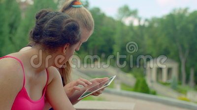 Girls using ipad in park. Students networking on tablet in park stock video footage