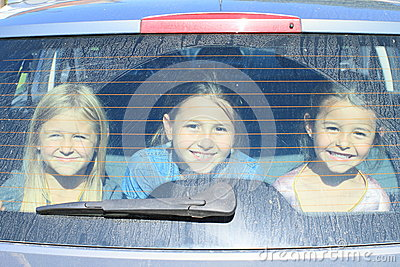 Girls watching from car trunk