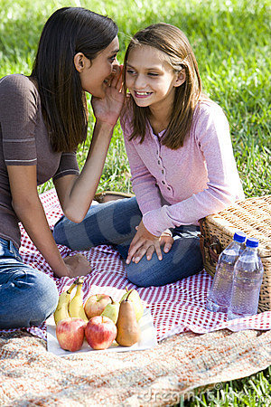 Girls whispering on picnic blanket on grass