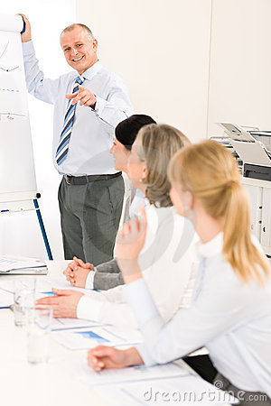 Giving presentation mature businessman at meeting