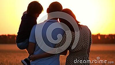 Glückliche Familie, die den Sonnenuntergang, stehend auf einem Weizengebiet aufpasst Ein Mann, der ein Kind in seinen Armen hält  stock video
