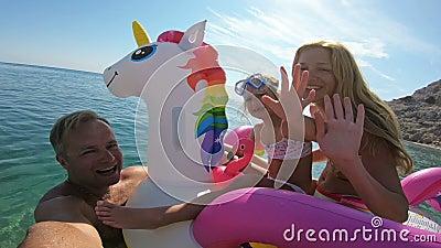 Glückliche Familie mit dem Mädchen, das selfie in den Seesitzplätzen auf dem aufblasbaren Einhorn nimmt stock footage