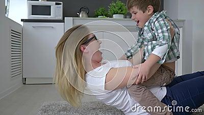 Glückliche Familie, weiblich mit dem Kind, das den Spaß zu Hause liegt auf Boden hat stock video footage